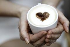 La fille tient une tasse de café avec le coeur de la cannelle Photos stock