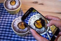 La fille tire la nourriture avec un smartphone Photographie stock