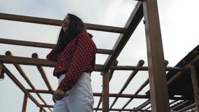 La fille tire un doigt sur le fond des constructions en bois banque de vidéos