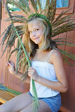 La fille tisse une guirlande d'herbe Photographie stock libre de droits