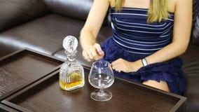 La fille touche timide la carafe avec de l'alcool et un gobelet en verre banque de vidéos