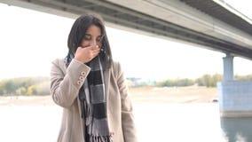 La fille tousse en parc Femme de Brunette de verticale jeune E banque de vidéos