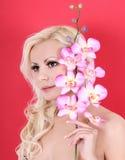 La fille très belle avec l'orchidée fleurit sur le rouge photographie stock libre de droits