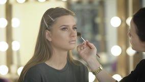 La fille très belle avec le maquillage lumineux et les lèvres luxuriantes jette un coup d'oeil souvent à l'appareil-photo tandis  banque de vidéos