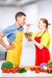 la fille traite son amant avec de la salade de légume frais, qu'ils ont faite cuire ensemble photographie stock libre de droits