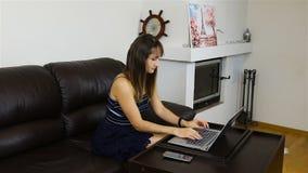La fille travaille avec un ordinateur portable sur un sofa dans le salon banque de vidéos