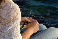 La fille tricote sur les rivages de la mer Méditerranée Photo stock