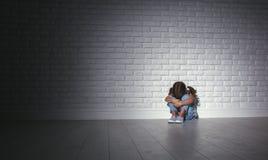 La fille triste triste bouleversée d'enfant dans l'effort pleure à un mur foncé vide