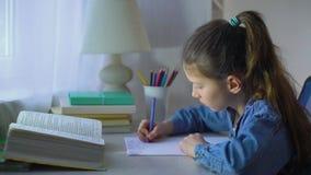 La fille triste d'école n'a pas fait des devoirs et n'a pas mis sa tête sur des mains banque de vidéos