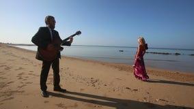 La fille triste en rouge danse près du guitariste contre des falaises au lever de soleil banque de vidéos