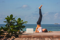 La fille a une pratique en matière de yoga sur le plancher en bois avec l'ordinateur portable Photo stock