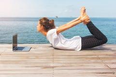 La fille a une pratique en matière de yoga sur le plancher en bois avec l'ordinateur portable Photographie stock libre de droits