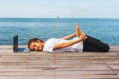 La fille a une pratique en matière de yoga sur le plancher en bois avec l'ordinateur portable Images libres de droits