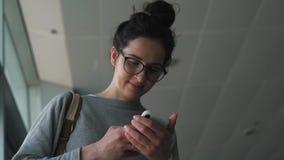 La fille utilise le smartphone dans le salon d'aéroport banque de vidéos
