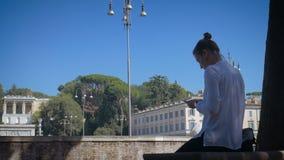 La fille utilise un smartphone sur Piata di Popolo à Rome ensoleillé banque de vidéos