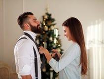 La fille vêtent son lien d'ami sur l'arbre de Noël de fond Image stock