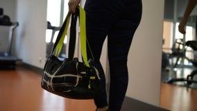 La fille va au gymnase Dans le cadre des sports mettez en sac les jambes, entre dans le vestiaire 4K MOIS lent clips vidéos
