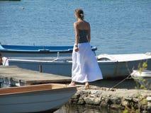 La fille va le long de la plage un jour ensoleillé en avant du pont en bois auquel les bateaux sont attachés image stock