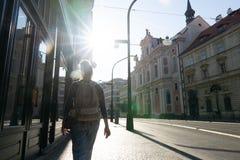 La fille va sur le trottoir dans la ville de matin à l'encontre le soleil soleil photos stock