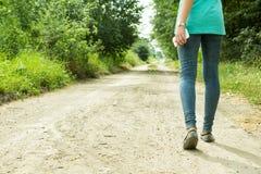 La fille va sur un chemin de terre avec un téléphone Photos libres de droits