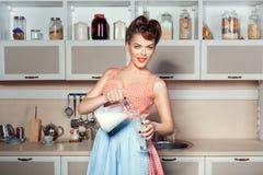 La fille verse le lait d'une cruche Images stock
