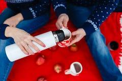 La fille verse le thé dans une tasse avec une photo du coeur Les jeunes couples dans des chandails se reposent sur la couverture  Photographie stock