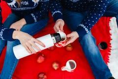 La fille verse le thé dans une tasse avec une photo du coeur Les jeunes couples dans des chandails se reposent sur la couverture  Photographie stock libre de droits