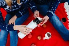La fille verse le thé dans une tasse avec une photo du coeur Les jeunes couples dans des chandails se reposent sur la couverture  Images libres de droits