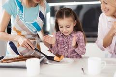 La fille veut vraiment essayer le tarte Une femme la met un morceau sur un plat Image stock