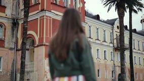 La fille vient à un grand beau monastère banque de vidéos