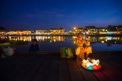 La fille vietnamienne vend les bougies de flottement sur le pont de Hoi An la nuit Photographie stock libre de droits
