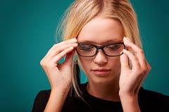 La fille voit mieux en tant qu'essai de nouveaux verres prescrits commandés dans le magasin images stock