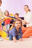 La fille vont cependant des cercles jouant le jeu dans le jardin d'enfants Photo libre de droits