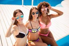 La fin a cultivé le coup courbe de trois dames mignonnes, posant I Photo stock