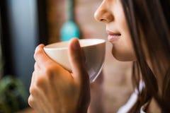 La fin d'une femme remet tenir une tasse de café chaude dans la boutique de café Image stock