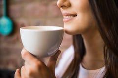 La fin d'une femme remet tenir une tasse de café chaude dans la boutique de café Photographie stock libre de droits