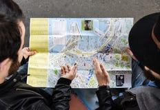 La fin de deux touristes masculins d'amis reposent la recherche sur la carte Image libre de droits