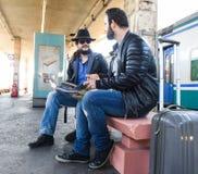 La fin de deux touristes masculins d'amis reposent la recherche sur la carte Images stock