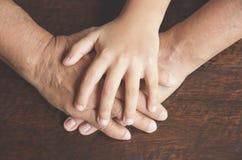 La fin de l'aîné et l'enfant joignent des mains Photographie stock libre de droits