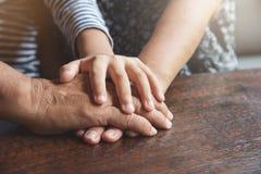 La fin de l'aîné et l'enfant joignent des mains Images stock