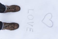 La fin de la chaussure des hommes vers le haut de la vue avec le simbol d'amour wrtien sur la neige Image stock
