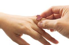La fin de la main de l'homme met l'anneau de forme de coeur au doigt d'anneau de la femme Photos libres de droits
