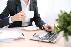La fin des mains de femme d'affaires avec une tasse de café se repose à la table et dactylographie sur un ordinateur portable dan Images libres de droits