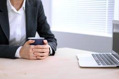 La fin des mains de femme d'affaires avec une tasse de café se repose à la table et dactylographie sur un ordinateur portable dan Image stock