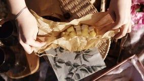 La fin des mains femelles ouvrent un petit sac de papier avec du fromage coupé en cubes Glaces de vin Concept de pique-nique Long clips vidéos
