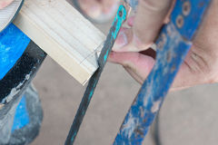 La fin du charpentier sciant un conseil avec du bois de main a vu Images stock
