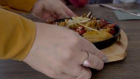 La fin du plat asiatique délicieux est placée à la table en bois par la serveuse dans le restaurant, mouvement lent banque de vidéos