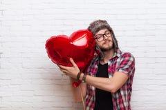 La fin rouge de Baloon de forme de coeur d'étreinte d'homme observe le style de mode de hippie Images stock
