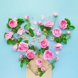 La fin vers le haut de la disposition créative avec les fleurs roses de thé rose, feuilles volent hors de l'enveloppe croped de p Photos stock
