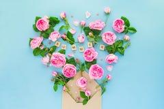 La fin vers le haut de la disposition créative avec les fleurs roses de thé rose, feuilles volent hors de l'enveloppe croped de p Images libres de droits